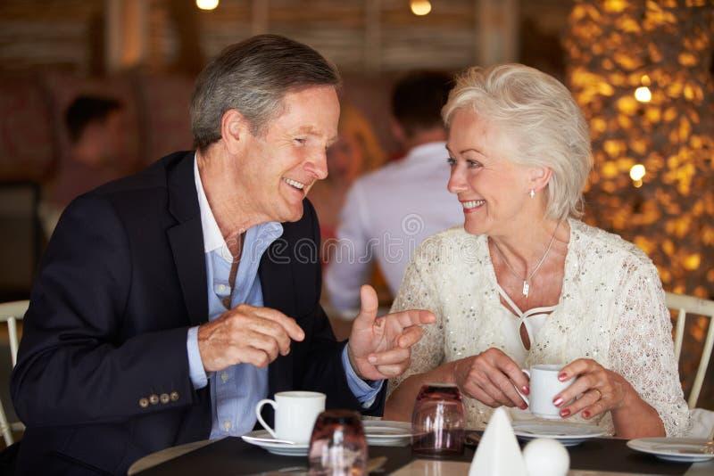 Höga par som tycker om koppen kaffe i restaurang royaltyfri foto