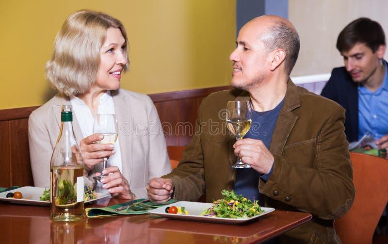 Höga par som tycker om mat i restaurang fotografering för bildbyråer