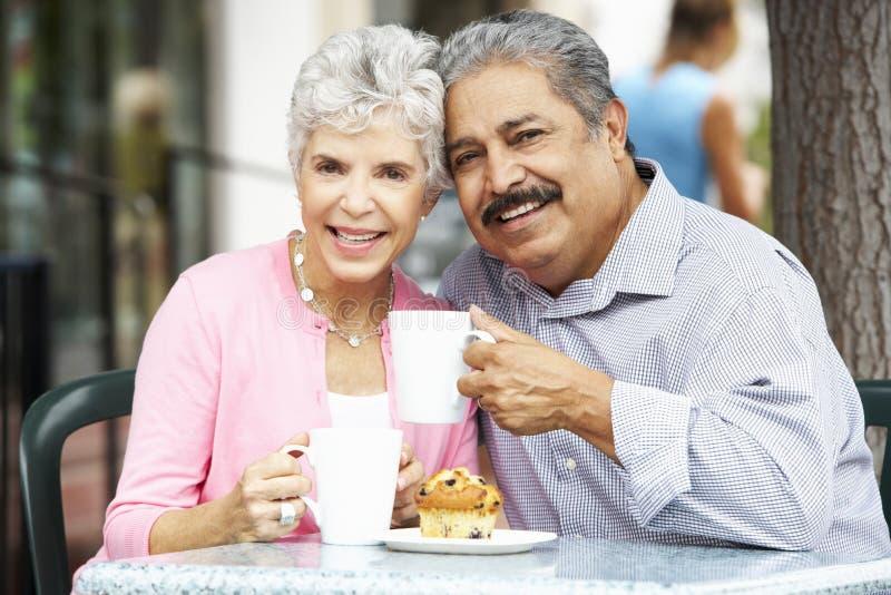 Höga par som tycker om mellanmålet på utomhus- CafÅ ½ royaltyfri fotografi