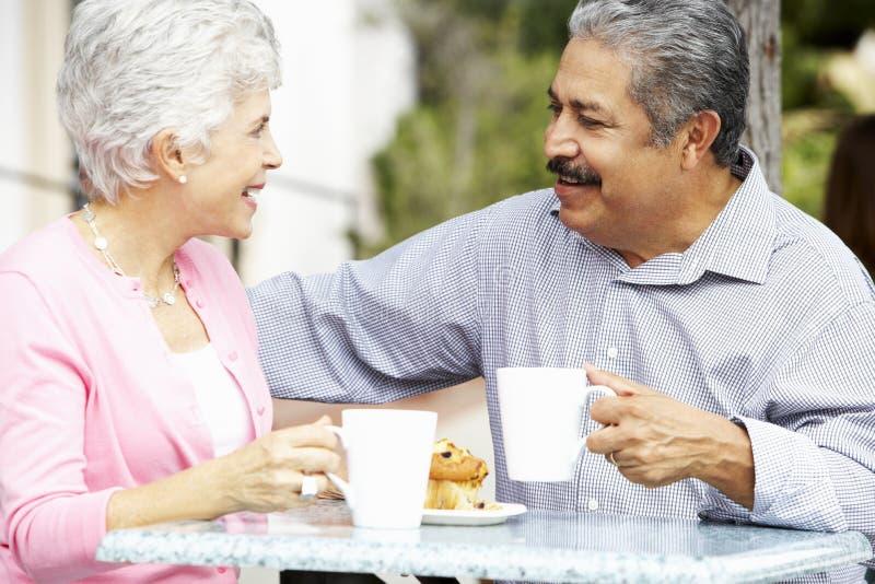 Höga par som tycker om mellanmålet på utomhus- CafÅ ½ royaltyfri bild