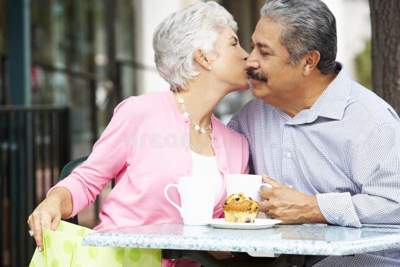 Höga par som tycker om mellanmålet på utomhus- CafÅ ½, når att ha shoppat royaltyfria bilder