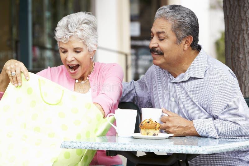 Höga par som tycker om mellanmålet på utomhus- CafÅ ½, når att ha shoppat arkivbild