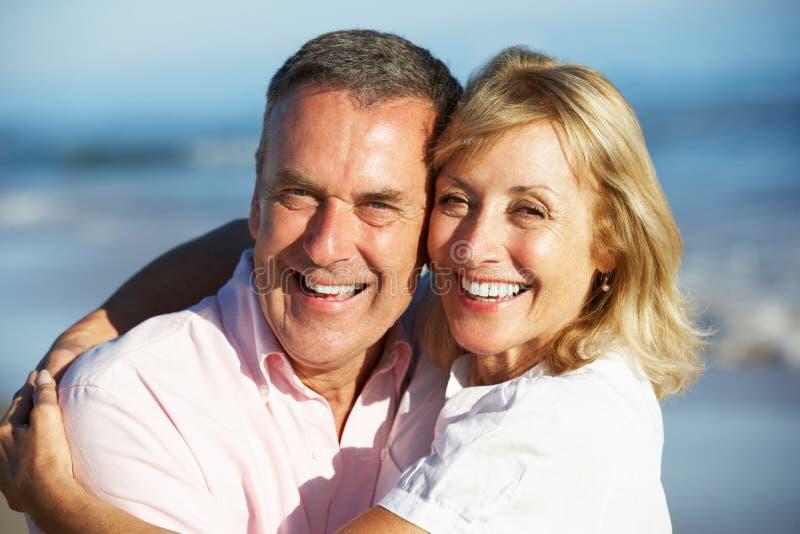 Höga par som tycker om romantisk strandferie arkivbilder