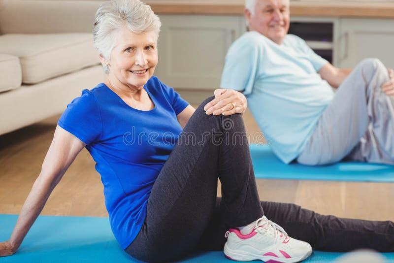 Höga par som utför yogaövning royaltyfri fotografi