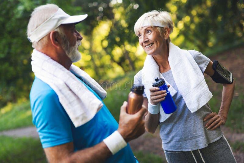 Höga par som utomhus joggar och kör i natur royaltyfria bilder
