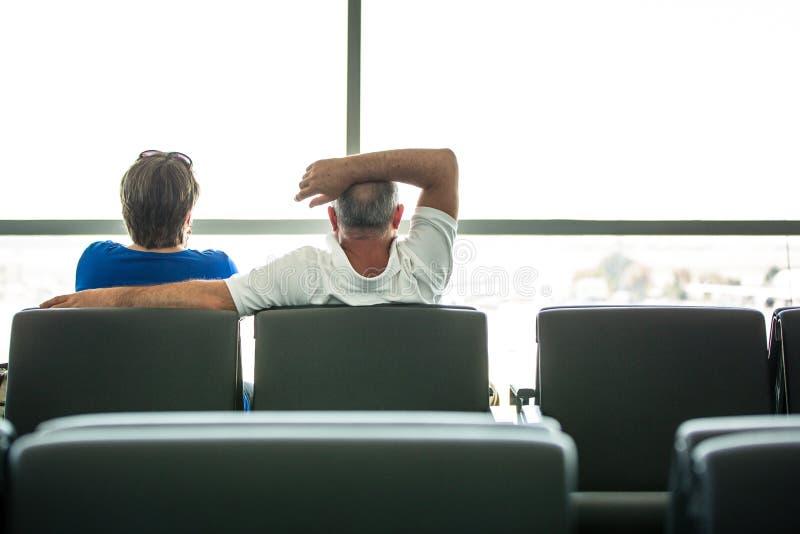 Höga par som väntar på deras flyg i en flygplats arkivbilder