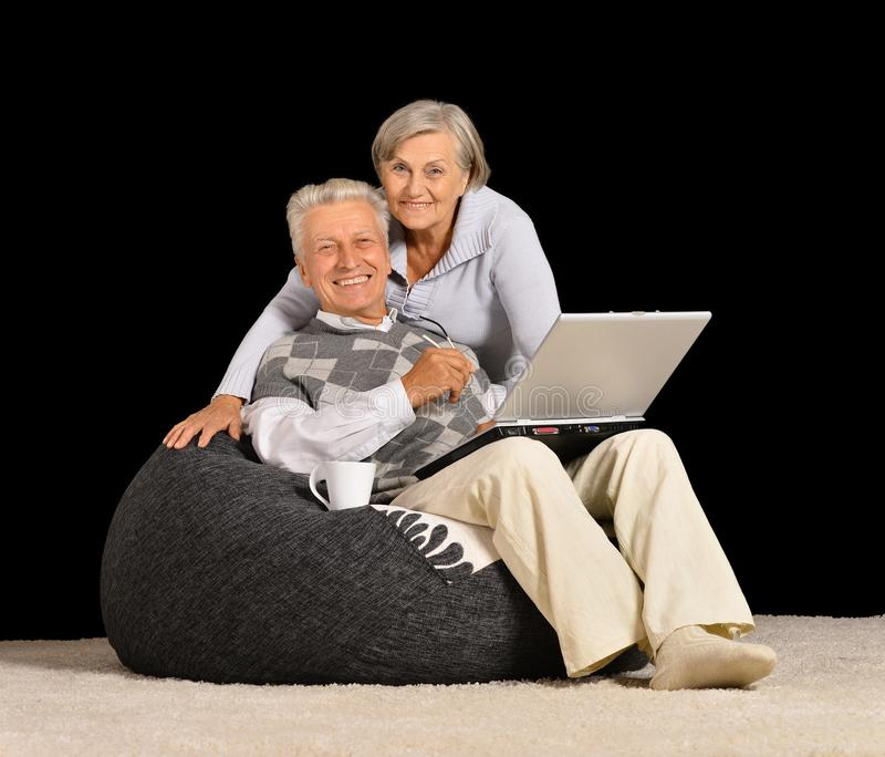 Höga par som vilar med bärbara datorn royaltyfri fotografi