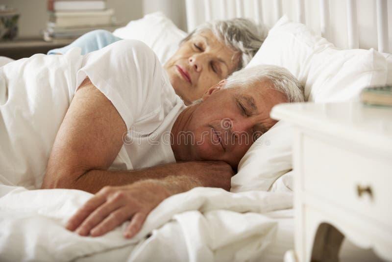 Höga par sovande i säng tillsammans arkivbild