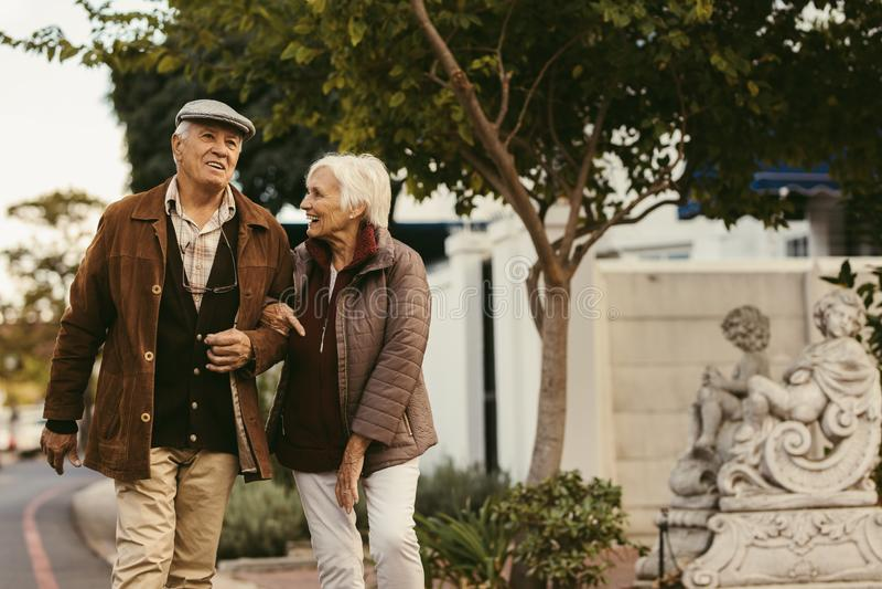 Höga par tycker om en gå tillsammans på en vinterdag fotografering för bildbyråer