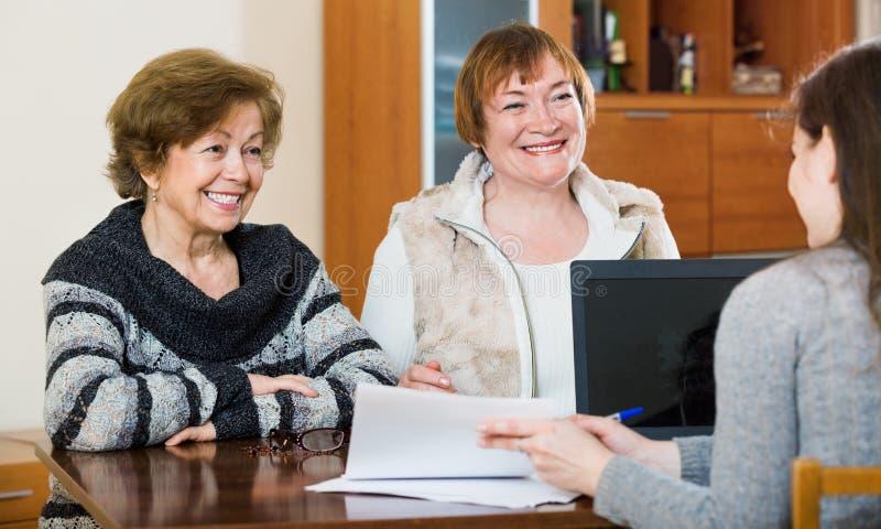 Höga positiva kvinnor som gör skallr på det offentliga notarius publicukontoret arkivbild