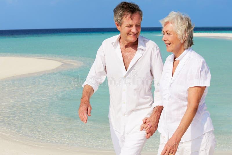 Höga romantiska par som går på den härliga tropiska stranden fotografering för bildbyråer