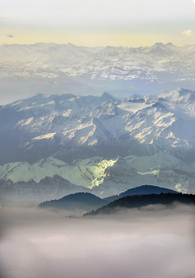 Höga snöig berg ovanför moln royaltyfri bild