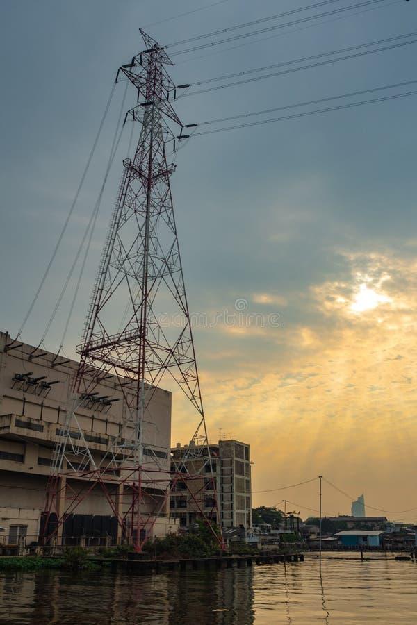 Höga spänningsöverföringstorn med den molniga soluppgånghimlen royaltyfria foton