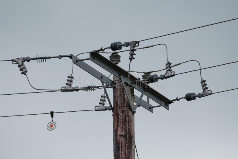 Höga spänningselströmkablar och isolatorer som ses på träpoler fotografering för bildbyråer