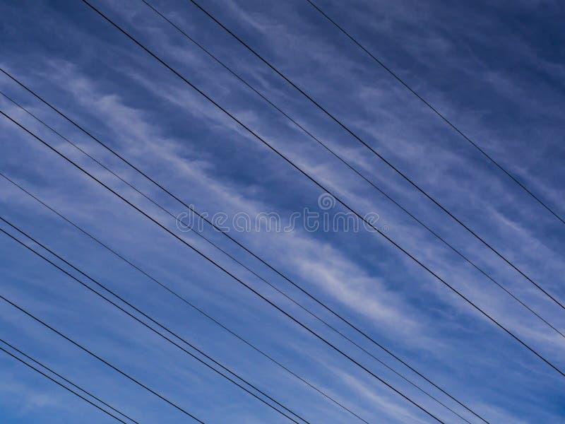 höga spänningskablar mot himlen arkivfoto