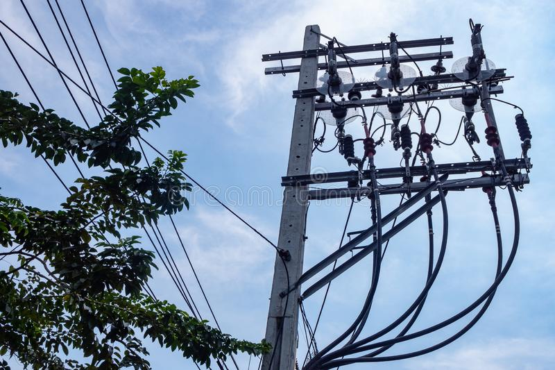 Höga spänningstrådar och elektrisk utrustning på konkreta poler arkivbild