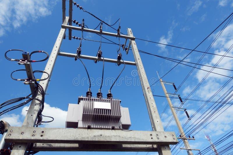 Höga spänningstransformatorer med kraftledningar och backgrou för blå himmel arkivbild