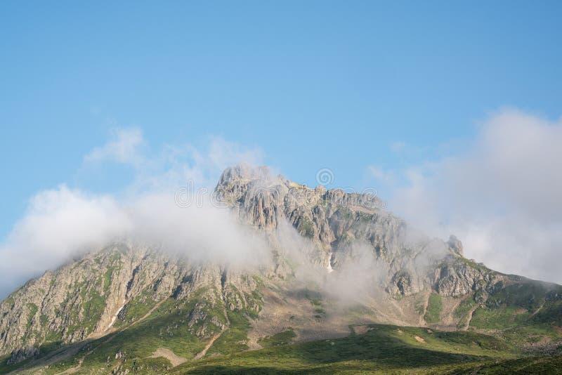 Höga stora berg och ängar i de Kackar bergen Härlig blå himmel, gräs och fördunklar royaltyfri foto