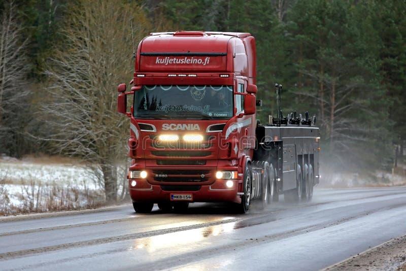 Höga strålar för röd Skåne R560 lastbil på vintervägen arkivfoton