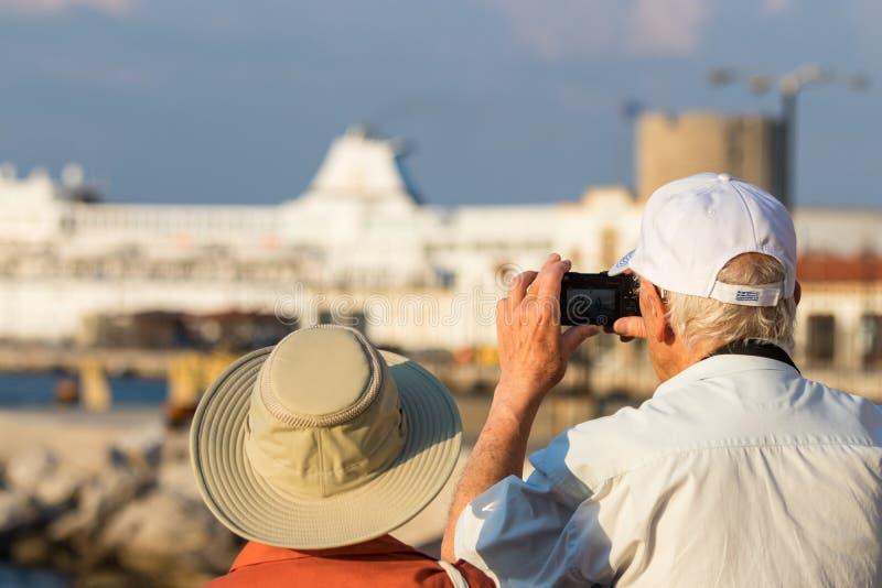 Höga turister för ett par som tar foto med en liten digital kamera på porten av Rhodos, Grekland royaltyfria foton