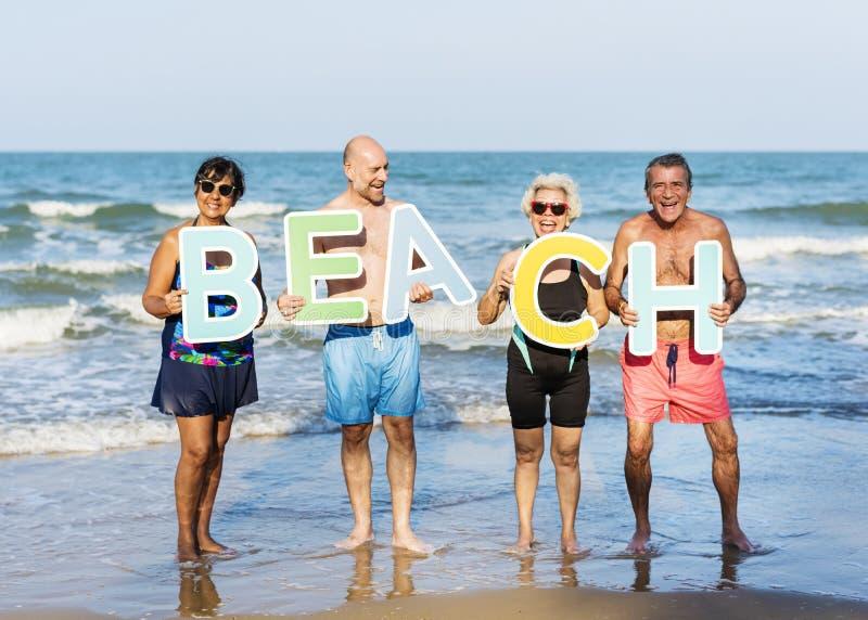 Höga vänner som har gyckel på stranden royaltyfri foto