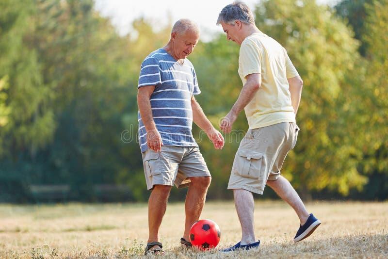 Höga vänner som spelar fotboll arkivbilder