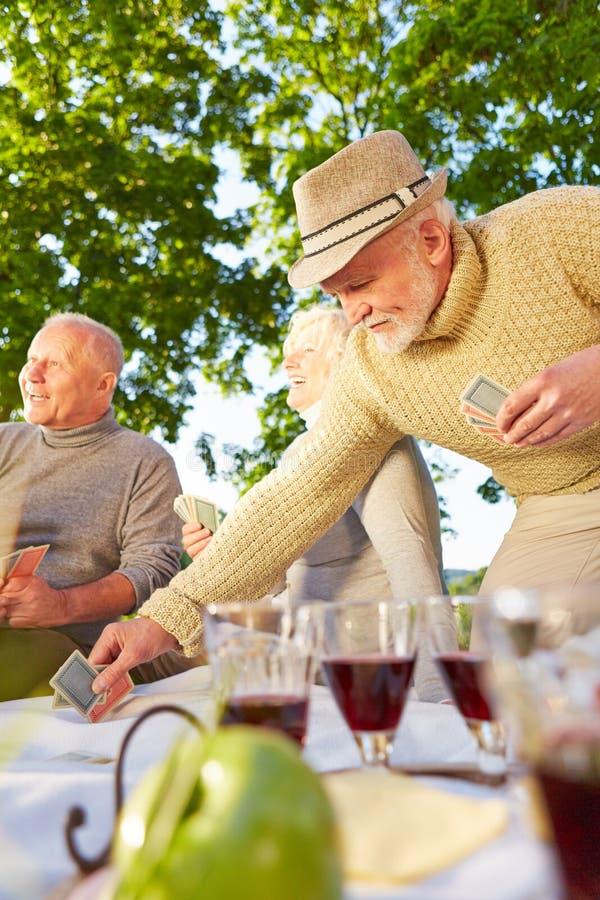 Höga vänner som spelar kort i en trädgård royaltyfri bild