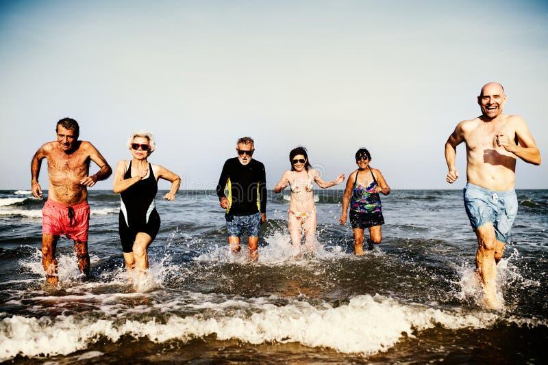 Höga vänner som tycker om stranden i sommartiden arkivbilder