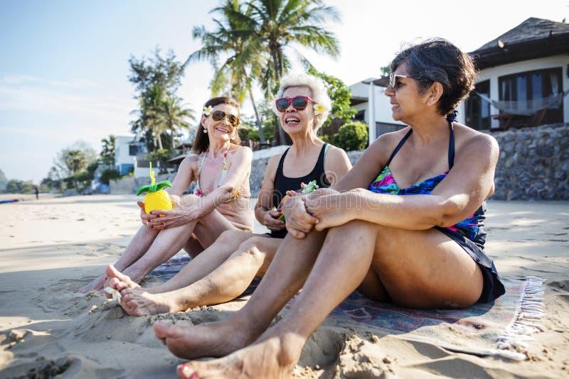 Höga vänner som tycker om stranden i sommartiden arkivfoto