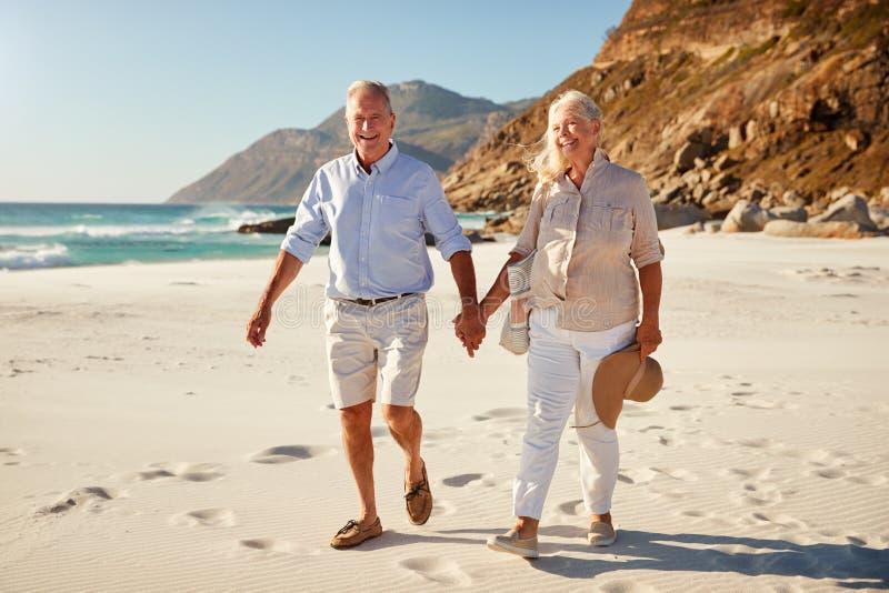 Höga vita par som går på en strand som tillsammans rymmer upp händer, full längd, slut royaltyfri foto