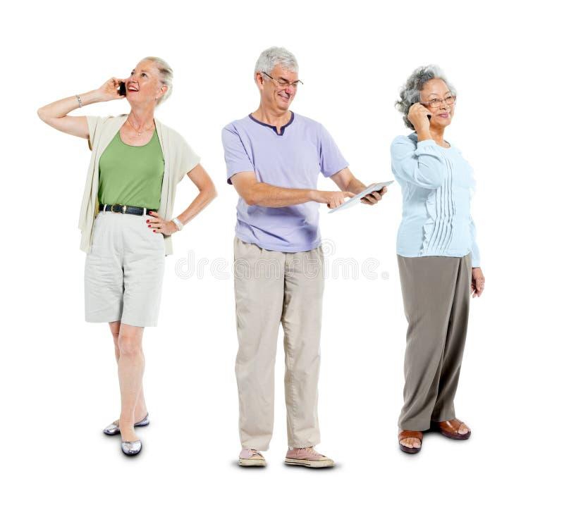 Höga vuxna människor som använder kommunikationsapparaten arkivbild