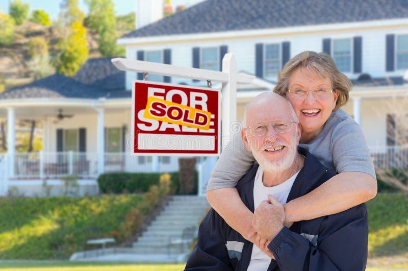 Höga vuxna par framme av det Real Estate tecknet, hus royaltyfri foto