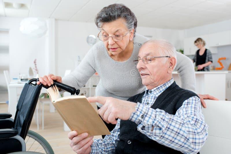 Höga vuxna par som hemma kontrollerar broschyren fotografering för bildbyråer