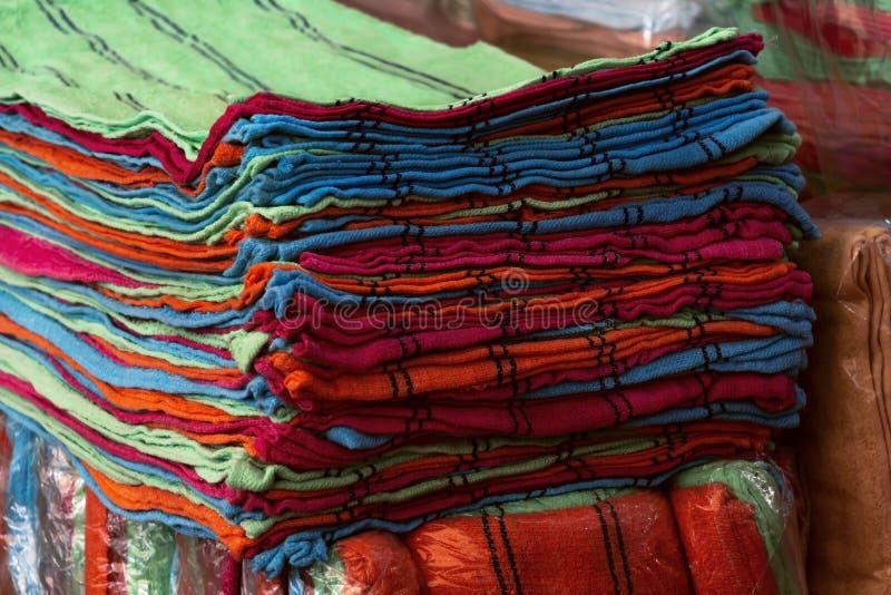 Högar av den färgrika handduken i olika färger som in staplas på hyllor arkivfoto