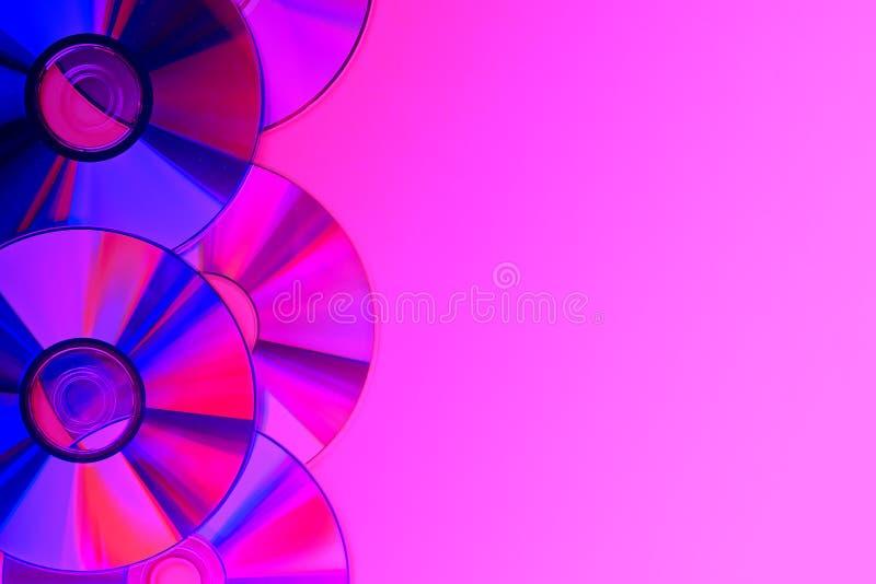 Högar av gammal och smutsig CD, DVD på rosa violett purpurfärgad neonbakgrund Använd dammig skiva med kopieringsutrymme royaltyfri foto