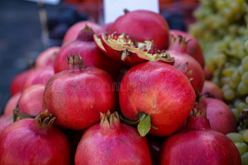 Högar av nytt härligt skinande mörker - röd granatäpplefrukt som säljer i lokal stadsmarknad med suddig bakgrund arkivfoton