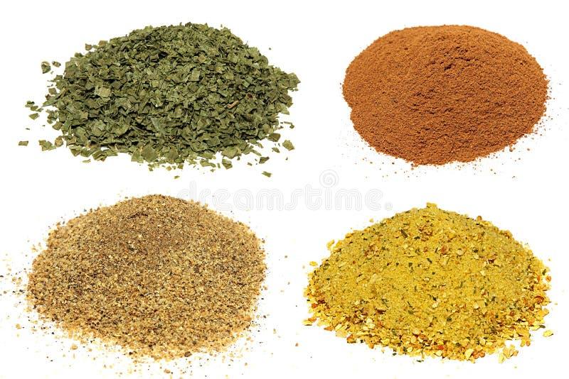Högar av olika kryddor som isoleras på vit royaltyfria foton