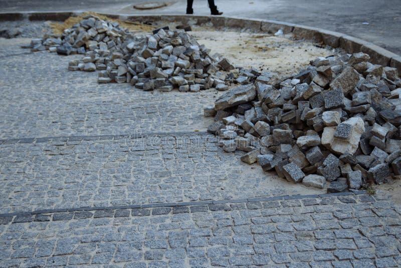 Högar av stenläggningstenar ligger på vägen som lägger stenar, oavslutat arbete fot- område för väg arkivbilder