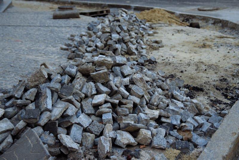 Högar av stenläggningstenar ligger på vägen som lägger stenar, oavslutat arbete fot- område för väg arkivfoto