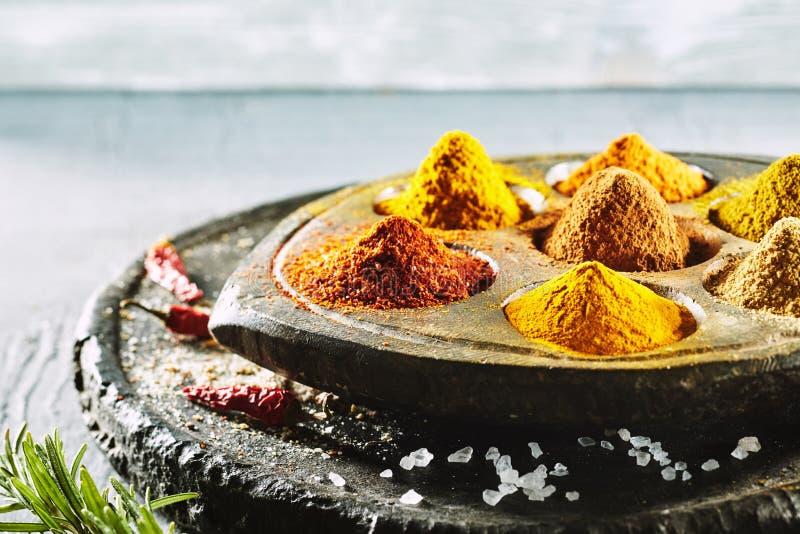 Högar av varma bittra kryddor på en tappningplatta royaltyfria bilder