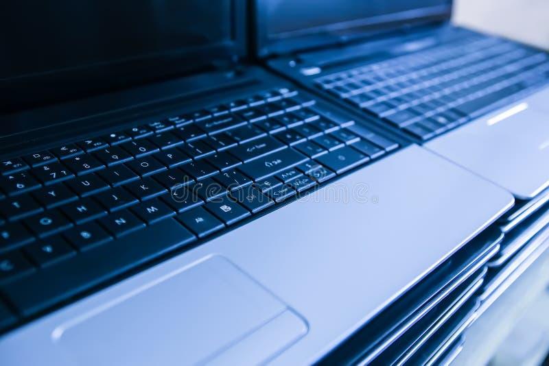 Högar på bärbara datorer med öppna tangentbord arkivfoton
