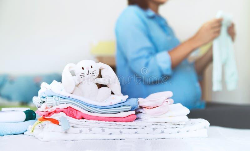 Högen av behandla som ett barn kläder, material och gravida kvinnan i hemmiljö arkivfoton