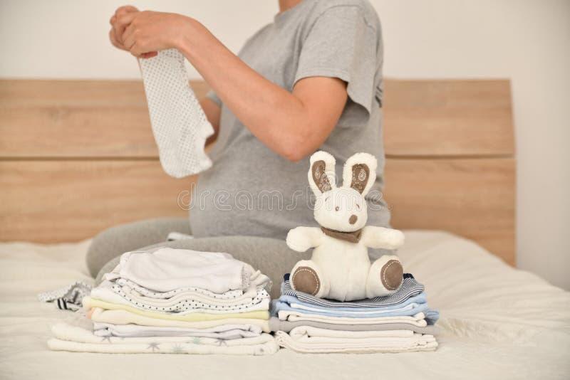 Högen av behandla som ett barn kläder och gravida kvinnan på en säng royaltyfri foto