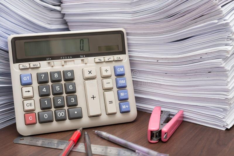 Högen av dokument på skrivbordet staplar upp högt arkivbild