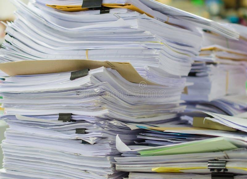 Högen av dokument på skrivbordet staplar upp högt att vänta som ska klaras av royaltyfri bild