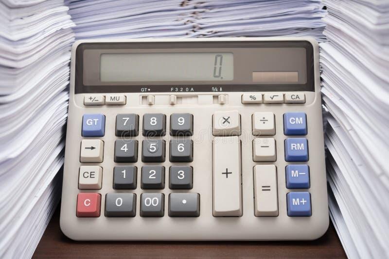 Högen av dokument på skrivbordet staplar upp högt med räknemaskinen arkivbilder