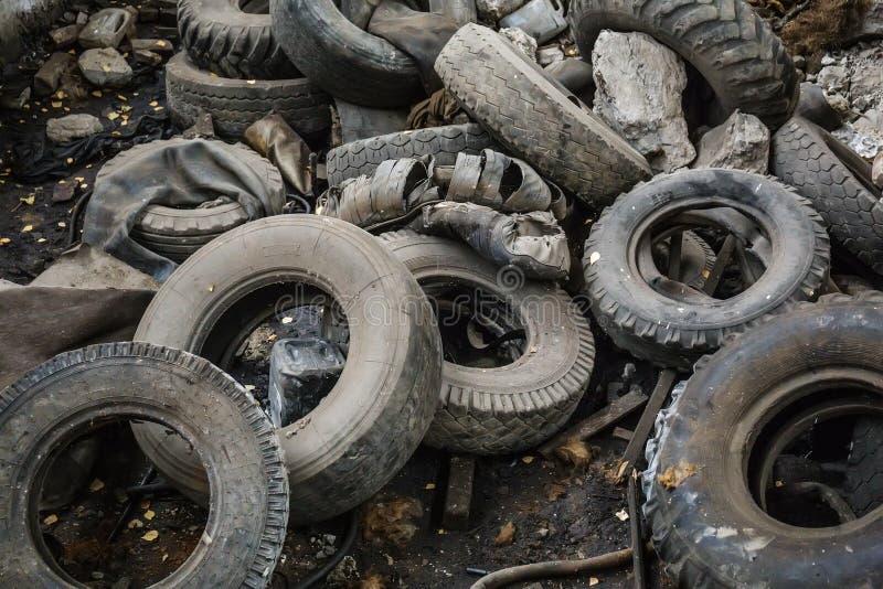 Högen av gamla bilskräpgummihjul, den använda lastbilen rackar ner på hjul, industriell avskräde arkivfoto