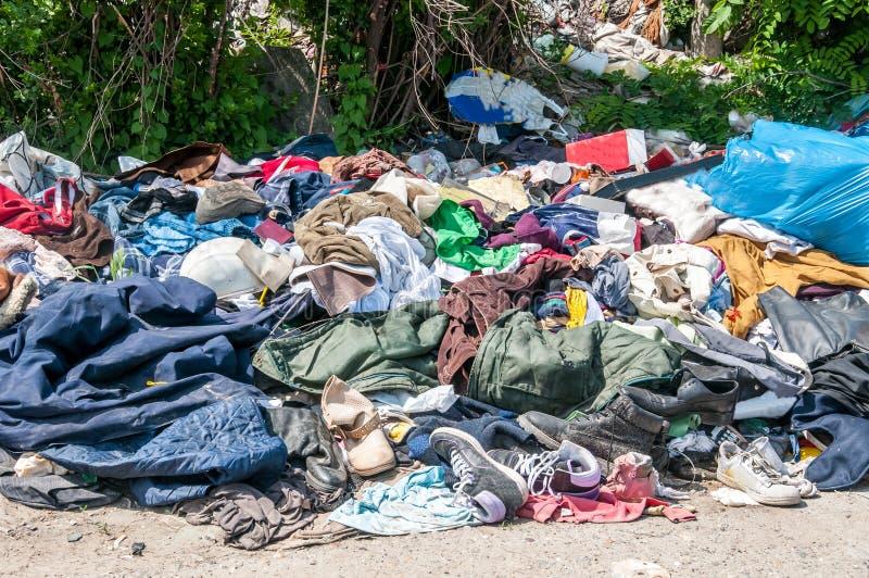 Högen av gamla kläder och skor dumpade på gräset som skräp och avskräde som skräpar ner och förorenar miljön arkivfoton