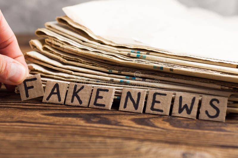 Högen av gamla tidningar bredvid mänskliga fingrar och papprektangelfyrkanter med den handskrivna inskriften fejkar nyheterna på  arkivbilder