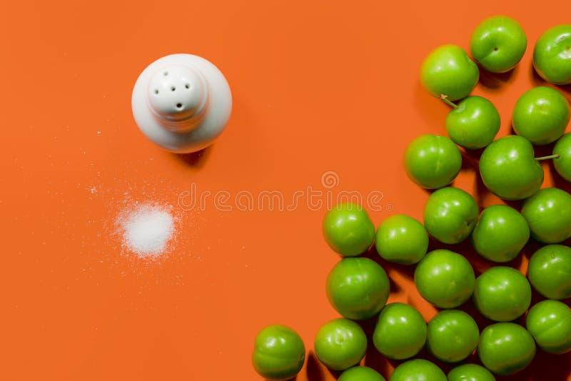 Högen av grön plommonfrukt med saltar isolerat på orange färgbakgrund royaltyfri foto